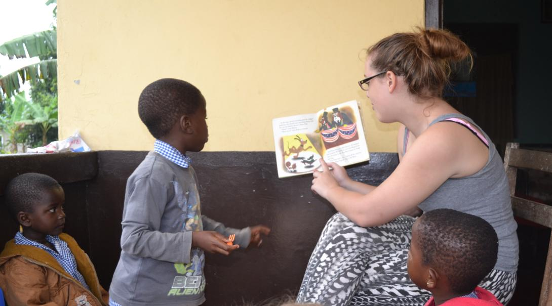 Voluntaria de Projects Abroad lee un libro a niños durante su trabajo voluntario en Ghana.